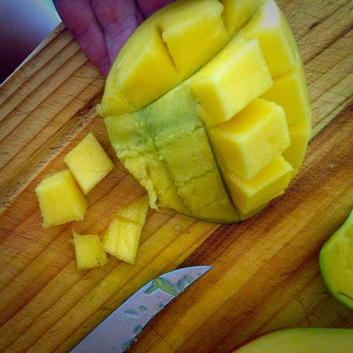 Helpful Hint: To easily cube a mango- slice the mango from around the pit. Holding the pieces of mango in your palm, slice horizontally then vertically but not through the skin. Flip the pieces of mango inside out and voila!